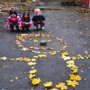 3 Kitakinder vor einem aus Blättern gelegten Männchen